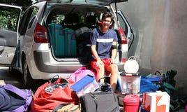Adolescente joven que se sienta en el coche con mucho equipaje Fotos de archivo