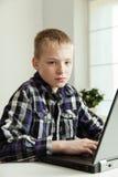 Adolescente joven que se sienta en el escritorio con el ordenador portátil Imagen de archivo libre de regalías