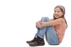 Adolescente joven que se sienta en el piso en blanco Foto de archivo