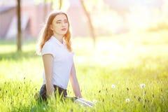 Adolescente joven que se sienta en hierba verde en parque Fotos de archivo libres de regalías