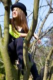 Adolescente joven que se sienta en la sonrisa de pensamiento del árbol Imagen de archivo
