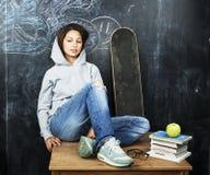 Adolescente joven que se sienta en sala de clase en la pizarra en la tabla, concepto de la gente de la educación de la forma de v Imagen de archivo