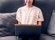Adolescente joven que se sienta en sofá y que usa el ordenador portátil a Imagen de archivo