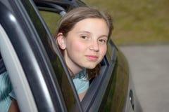 Adolescente joven que se sienta en un coche Foto de archivo