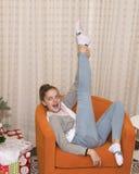 Adolescente joven que se sienta en una silla anaranjada con la pierna derecha que señala al techo Imagen de archivo