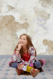 Adolescente joven que se sienta a piernas cruzadas en el piso Imagen de archivo libre de regalías