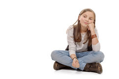 Adolescente joven que se sienta a piernas cruzadas en el piso en blanco Imágenes de archivo libres de regalías