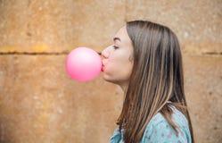 Adolescente joven que sopla el chicle rosado Foto de archivo