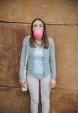 Adolescente joven que sopla el chicle rosado Imagenes de archivo