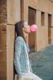 Adolescente joven que sopla el chicle rosado Imagen de archivo