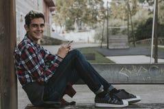 Adolescente joven que sostiene el teléfono móvil Imagen de archivo libre de regalías