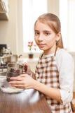 Adolescente joven que tamiza la harina a través del tamiz Foto de archivo libre de regalías