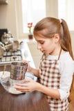 Adolescente joven que tamiza la harina a través del tamiz Imagenes de archivo