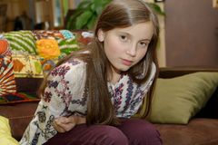 Adolescente joven que tiene un dolor de estómago que se sienta en el sofá Imágenes de archivo libres de regalías