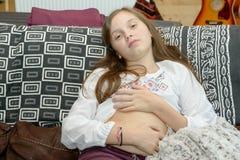 Adolescente joven que tiene un dolor de estómago que se sienta en el sofá Foto de archivo