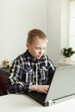 Adolescente joven que usa el ordenador portátil en el escritorio Fotografía de archivo