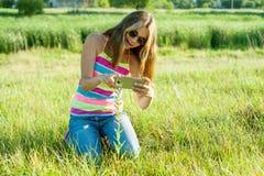 Adolescente joven que usa un smartphone, fotografiando una flor adentro Fotos de archivo libres de regalías
