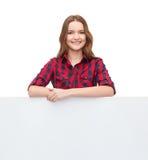 Adolescente joven sonriente con el tablero en blanco blanco Fotografía de archivo libre de regalías