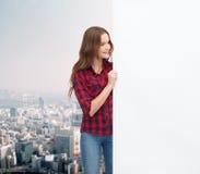 Adolescente joven sonriente con el tablero en blanco blanco Foto de archivo libre de regalías