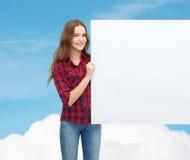Adolescente joven sonriente con el tablero en blanco blanco Imágenes de archivo libres de regalías