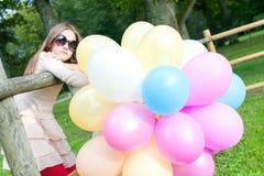 Adolescente joven sonriente hermoso con los globos multicolores Imagen de archivo libre de regalías