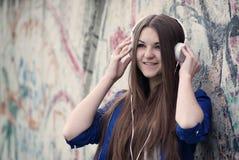 Adolescente joven sonriente que escucha la música Imagen de archivo libre de regalías