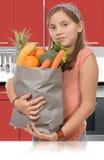 Adolescente joven, sosteniendo el bolso de compras con el suplente de las verduras Foto de archivo