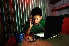 Adolescente joven usando un teléfono móvil o un smartphone delante de un ordenador portátil Fotos de archivo