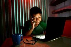 Adolescente joven usando un teléfono móvil o un smartphone delante de un ordenador portátil Foto de archivo