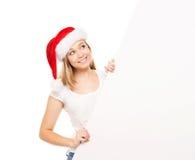 Adolescente joven y feliz en un sombrero de la Navidad que sostiene una bandera Foto de archivo libre de regalías
