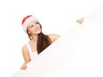 Adolescente joven y feliz en un sombrero de la Navidad que sostiene una bandera Fotografía de archivo libre de regalías