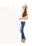 Adolescente joven y feliz en un sombrero de la Navidad que sostiene una bandera Fotos de archivo libres de regalías
