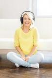 Adolescente joven y hermoso que escucha la música en casa Fotografía de archivo