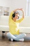Adolescente joven y hermoso que escucha la música en casa Foto de archivo libre de regalías