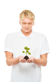 Adolescente joven y hermoso que sostiene el suelo con una planta Fotografía de archivo libre de regalías