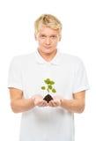 Adolescente joven y hermoso que sostiene una planta Fotos de archivo libres de regalías