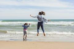 Adolescente joven y niña que saltan en la orilla de la playa Imagenes de archivo