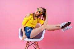 Adolescente juguetón que se sienta en silla con las piernas aumentadas Fotos de archivo