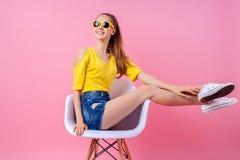 Adolescente juguetón que se sienta en silla con las piernas aumentadas Imágenes de archivo libres de regalías