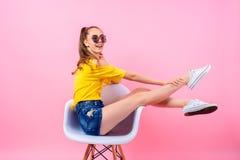 Adolescente juguetón que se sienta en silla con las piernas aumentadas Foto de archivo
