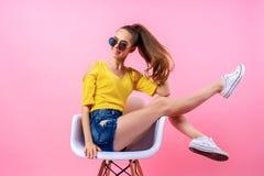 Adolescente juguetón que se sienta en silla con las piernas aumentadas Fotos de archivo libres de regalías