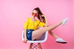 Adolescente juguetón que se sienta en silla con las piernas aumentadas Fotografía de archivo libre de regalías