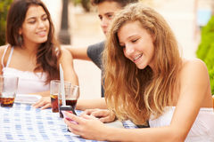 Adolescente à l'aide du téléphone portable se reposant au ½ de ¿ de Cafï avec des amis Photos stock