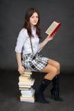 Adolescente lee en una pila de libros en backgrou negro Foto de archivo libre de regalías