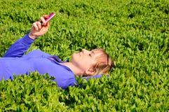 Adolescente lee sms Imagen de archivo libre de regalías