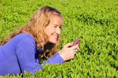 Adolescente lee sms y sonríe Imagenes de archivo
