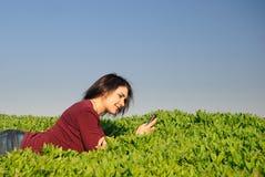 Adolescente lee sms y sonríe Fotografía de archivo libre de regalías