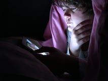 Adolescente a letto a letto alla notte, facendo uso di un dispositivo digitale immagini stock libere da diritti