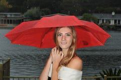 Adolescente lindo bajo el paraguas rojo Foto de archivo