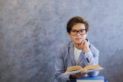 Adolescente lindo con el libro de lectura de los vidrios Fotos de archivo